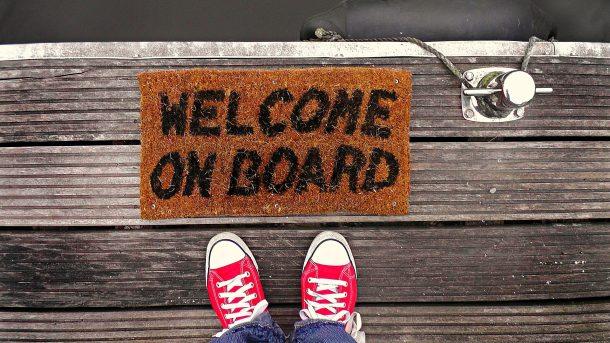 voeten die voor de deurmat welcome on board staan